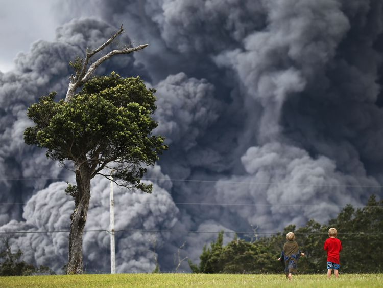 Boys look on from a  golf course as an ash plume rises in the distance