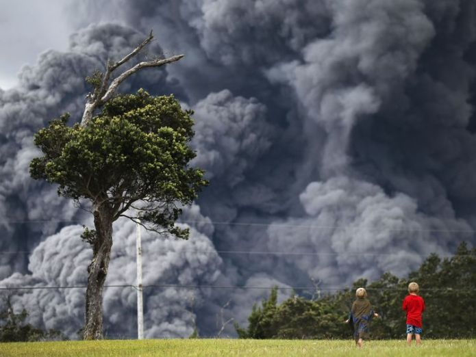 Boys look on from a  golf course as an ash plume rises in the distance Roads ripped up by rumbling Big Island Hawaii volcano Roads ripped up by rumbling Big Island Hawaii volcano skynews kilauea volcano hawaii 4312273