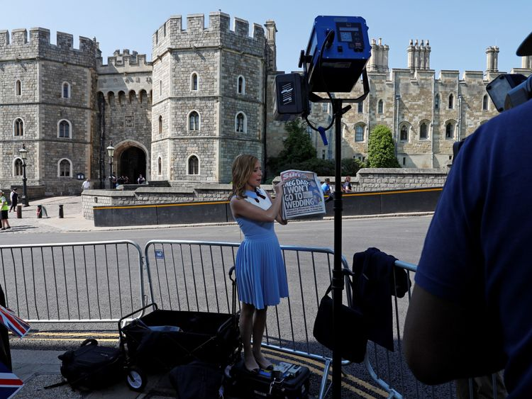 A television reporter for the US network CNN, holds up copies of today's British newspapers leading with a story of Meghan Markle's father Thomas Markle, opposite the Henry VII Gate of Windsor Castle in Windsor