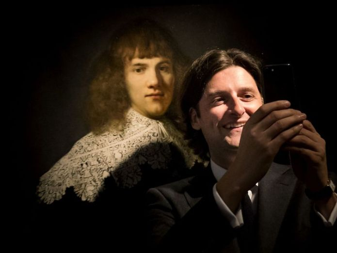 Amsterdam art dealer and historian Jan Six (R) takes a 'selfie' as he stands beside 'Portrait of a Young Gentleman' by Rembrandt van Rijn  Art dealer discovers unknown Rembrandt missed by Christie's Art dealer discovers unknown Rembrandt missed by Christie's skynews rembrandt amsterdam 4311826