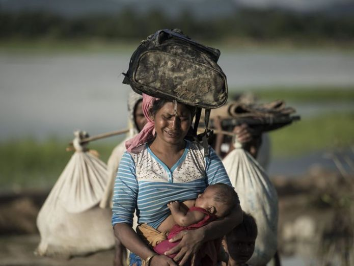 PSHOT - Rohingya refugee cries as she walks after crossing the Naf river from Myanmar into Bangladesh in Whaikhyang on October 9, 2017. A top UN official said on October 7 Bangladesh's plan to build the world's biggest refugee camp for 800,000-plus Rohingya Muslims was dangerous because overcrowding could heighten the risks of deadly diseases spreading quickly. The arrival of more than half a million Rohingya refugees who have fled an army crackdown in Myanmar's troubled Rakhine state since Augu myanmar military could be investigated over rohingya abuses Myanmar military could be investigated over Rohingya abuses skynews rohingya refugee myanmar 4323904