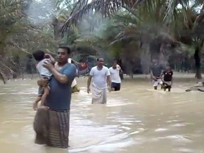 A man clutches a young child as he wades through floodwater in Socotra Cyclone Mekunu leaves at least 10 dead as it batters Oman and Yemen Cyclone Mekunu leaves at least 10 dead as it batters Oman and Yemen skynews socotra cyclone mekunu 4320995