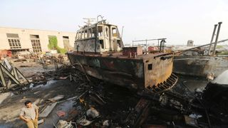 A worker walks past a tug damaged by an air strike on the maintenance hub at the Hodeida port, Yemen Saudi-led forces 'seize control of Hodeida airport' Saudi-led forces 'seize control of Hodeida airport' skynews yemen air strike hodeida port 4335759