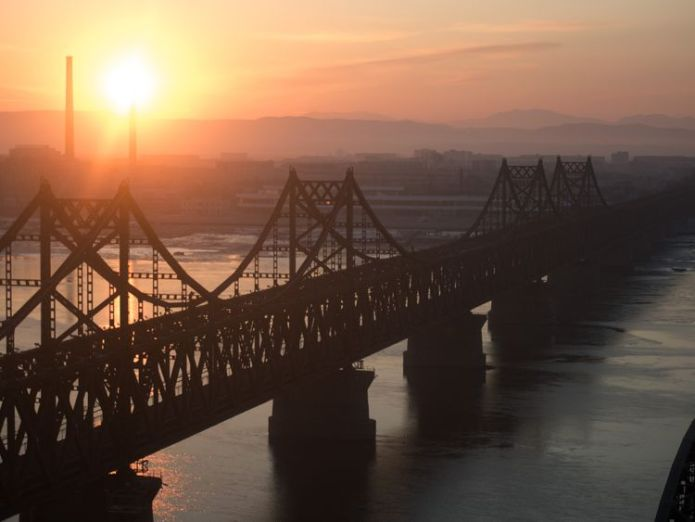 The sun rises over the bridge on the banks of the Yalu River in the Chinese border town of Dandong opposite to the North Korean town of Sinuiju on February 10, 2016 Kim doesn't want aid - he wants investment Kim doesn't want aid – he wants investment skynews dandong yalu china 4333043