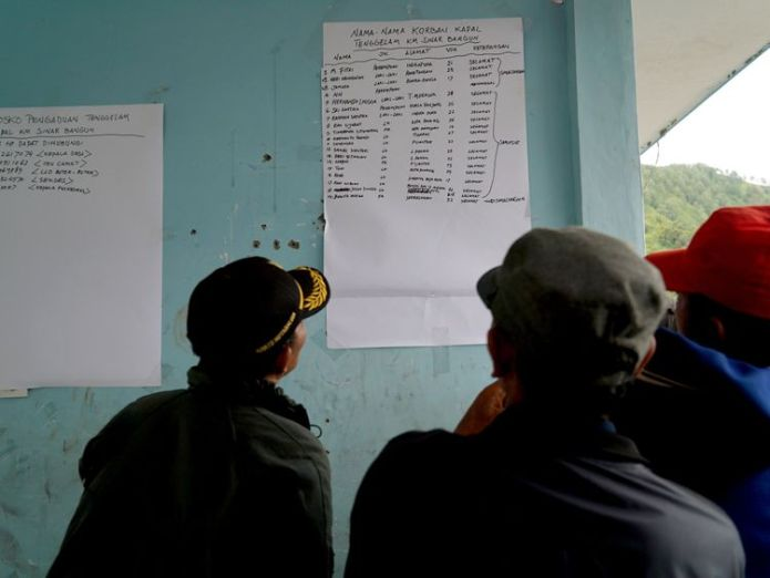 Family members look at a survivor list at the Lake Toba ferry port  Dozens feared dead and '128 missing' after ferry sinks in Indonesia Dozens feared dead and '128 missing' after ferry sinks in Indonesia skynews ferry indonesia ferry 4339955