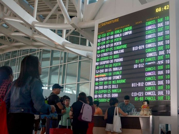 Travellers check their flights at Ngurah Rai airport in Denpasar, Bali which is closed on June 29, 2018 after a pilot report detected volcanic ash as high as 23,000 feet following Mount Agung's eruption. - Bali closed its international airport following a volcanic eruption on the Indonesian resort island that sent thick smoke and ash billowing 2,000 metres (6,500 feet) into the air, an official said. (Photo by GEDE ARDIASA / AFP) (Photo credit should read GEDE ARDIASA/AFP/Getty Images)  Volcano eruption leaves thousands stranded in Bali skynews indoensia bali volcano 4348612