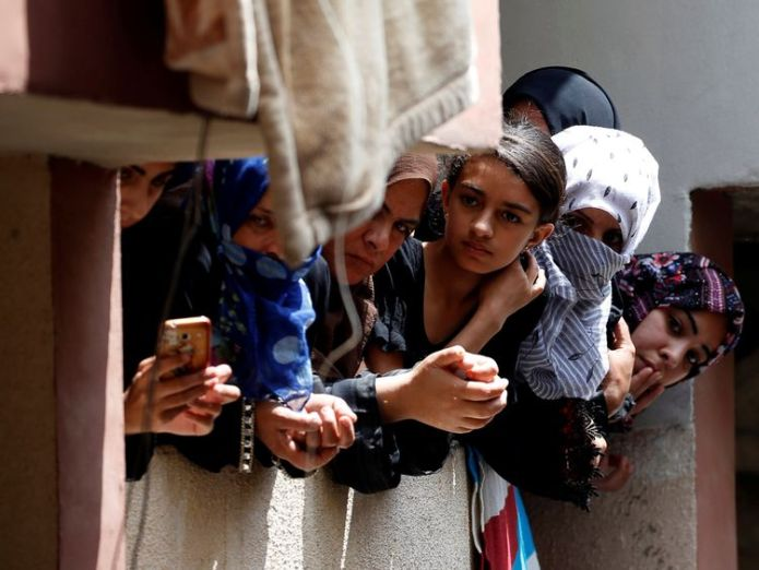 People hung out of windows to watch the funeral Medical official urges world 'not to keep silent' Medical official urges world 'not to keep silent' skynews razan al najar funeral 4326530