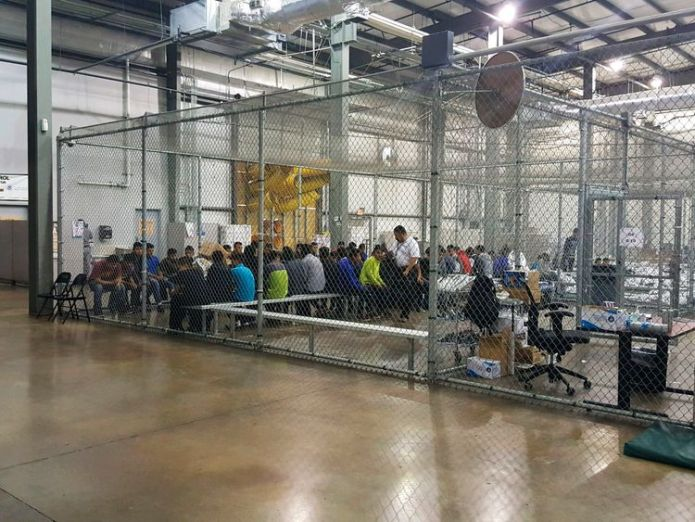 People sit on benches inside a cage in the facility Recording captures children's cries for parents at US border Recording captures children's cries for parents at US border skynews us border facility 4339094