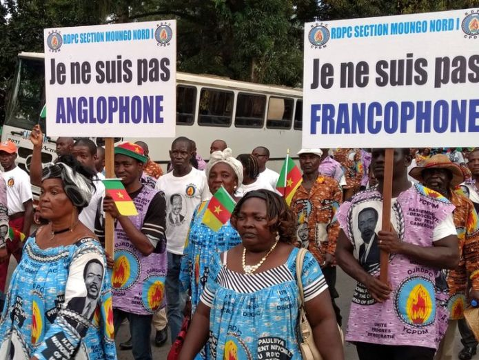 "Demonstrators carry banners as they take part in a march reading: ""I am not Francophone.""(R), ""I am not Anglophone"" (L)  'Grave abuses' as 180,000 people displaced in Cameroon skynews cameroon francophone 4366368"