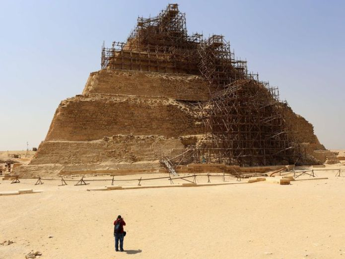 A tourists take a picture of the step pyramid of Djoser during a visit to the ancient Egyptian Saqqara necropolis some 20 kilometres south of Cairo on September 16, 2014. Egypt tried to end controversy about the restoration of the step pyramid of Djose, after facing accusations of endangering the famous pharaonic monument, dating back over 4,600 years, due to ongoing restoration work. AFP PHOTO/ MOHAMED EL-SHAHED (Photo credit should read MOHAMED EL-SHAHED/AFP/Getty Images)   Ancient Egyptian mummification workshop discovered skynews egypt saqqara 4362054