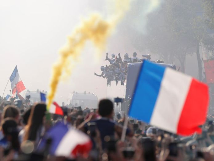 The players parade the trophy as flares are let off  France fans pack Champs Elysees in Paris to get glimpse of World Cup winners skynews france paris football 4363800
