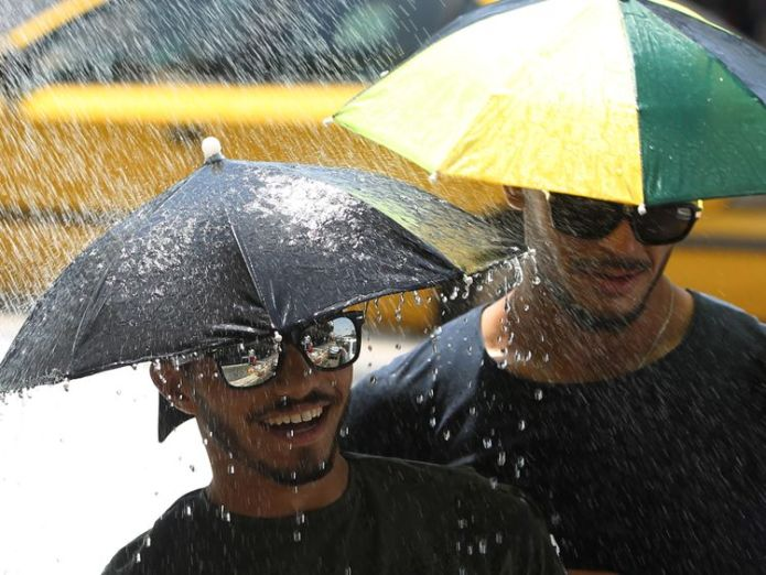 Iraqi men wear umbrellas to protect themself from the sun stand under a shower set up in a street in Baghdad because of the high temperature on July 5, 2018. - Iraq is witnessing very high temperatures and some cities in the southern part of the country were allowed to take a day off from work. (Photo by AHMAD AL-RUBAYE / AFP) (Photo credit should read AHMAD AL-RUBAYE/AFP/Getty Images)