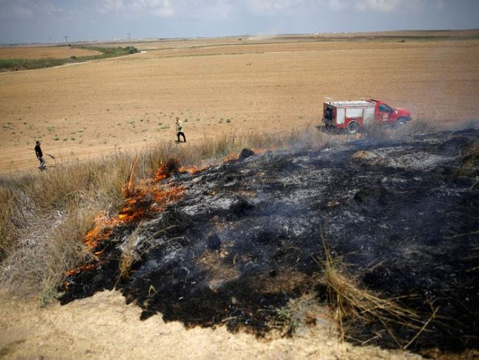 Israeli firefighters attempt to extinguish a fire burning scrubland in an area where Palestinians have been causing blazes by flying kites and balloons loaded with flammable materials, on the Israeli side of the border between Israel and the Gaza Strip July 20  Israeli soldier and four Palestinians killed in Gaza Strip clashes skynews israel palestinians 4367361