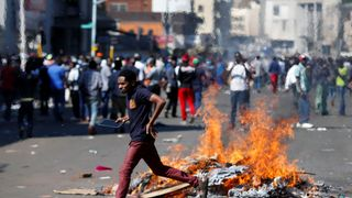 A man runs as supporters of the opposition Movement for Democratic Change party (MDC) of Nelson Chamisa burn barricades in Harare, Zimbabwe
