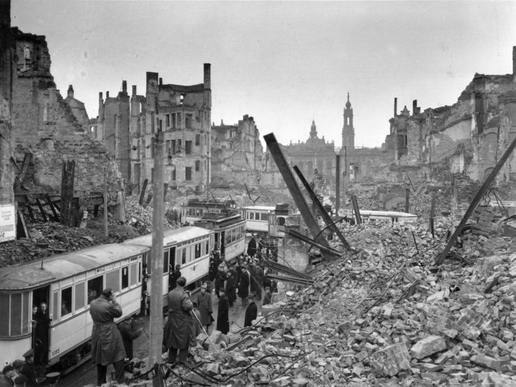 Germans board trams in the midst of ruins left by an Allied air raid on Johannstrasse, Dresden