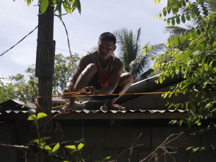 A man secures the roof of his house in Candon City, north of Manila  'Super typhoon' Mangkhut set to hammer the Philippines skynews typhoon mangkhut philippines 4420151