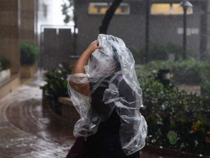A pedestrian uses a plastic poncho during Super Typhoon Mangkhut in Hong Kong on September 16, 2018. - Typhoon Mangkhut rocked Hong Kong en route to mainland China on September 16, injuring scores and sending skyscrapers swaying, after killing at least 30 people in the Philippines and ripping a swathe of destruction through its agricultural heartland. (Photo by Anthony WALLACE / AFP) (Photo credit should read ANTHONY WALLACE/AFP/Getty Images)