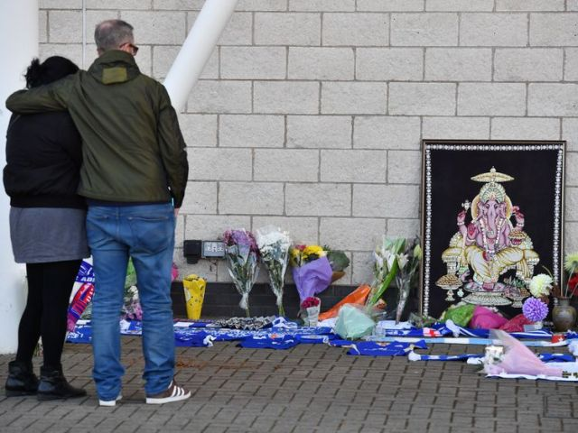 People react as they pause at floral tributes lined up outside Leicester City Football Club's King Power Stadium in Leicester, eastern England, on October 28, 2018 after a helicopter belonging to the club's Thai chairman Vichai Srivaddhanaprabha crashed outside the stadium the night before. - Leicester City's charismatic Thai chairman was the subject of growing concerns on October 28 after a helicopter belonging to the billionaire crashed and burst into flames in the stadium carpark shortly afte