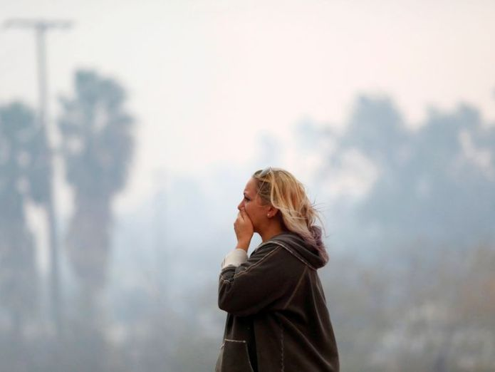 A woman reacts as the Woolsey Fire burns in Malibu, California, U.S. November 9, 2018  Eleven die in California fires after more bodies found skynews california fire woolsey 4483194