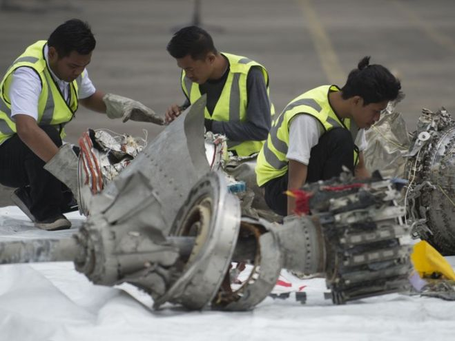 Investigators examine engine parts from the ill-fated Lion Air flight JT 610 at a port in Jakarta on November 7, 2018, after they were recovered from the bottom of the Java sea. - The Indonesian Lion Air jet that plunged into the Java Sea on October 29, killing all 189 on board, had an air speed indicator problem on its fatal flight and on three previous journeys, the country's transportation watchdog said on November 6. (Photo by BAY ISMOYO / AFP) (Photo credit should read BAY ISMOYO/AFP/Getty
