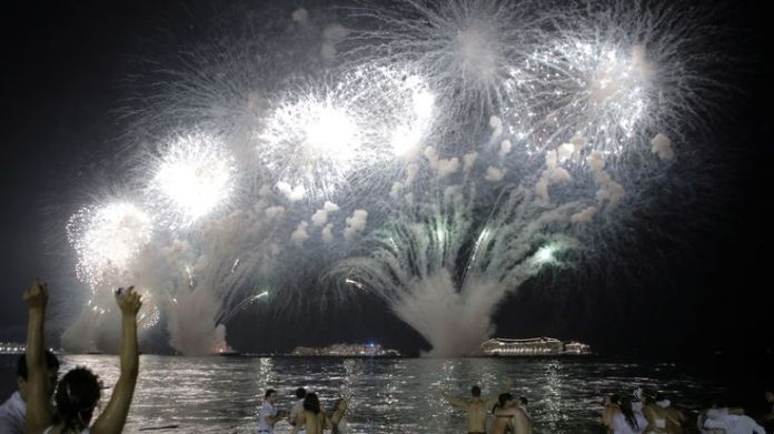 People watch as fireworks explode over Copacabana beach during New Year celebrations in Rio de Janeiro, Brazil January 1, 2019
