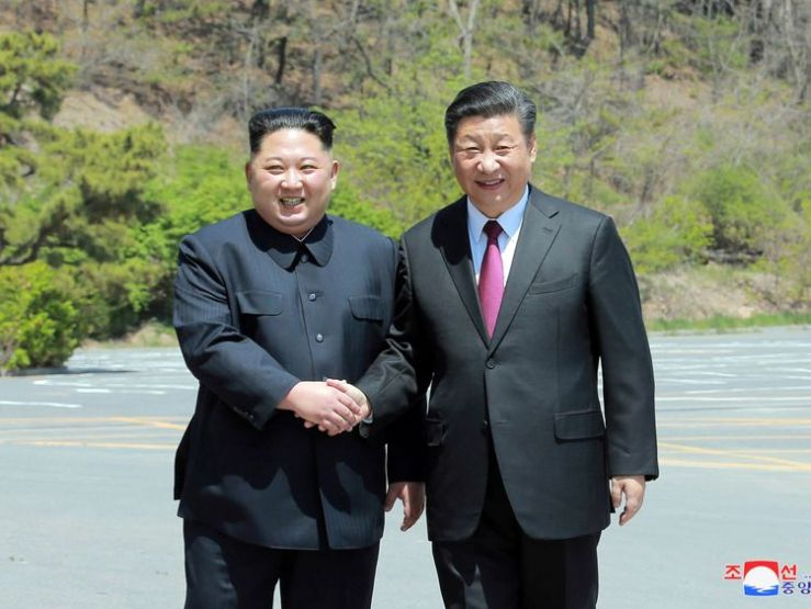 North Korean leader Kim Jong Un shakes hands with China's President Xi Jinping, in Dalian, China in this undated photo released on May 9, 2018