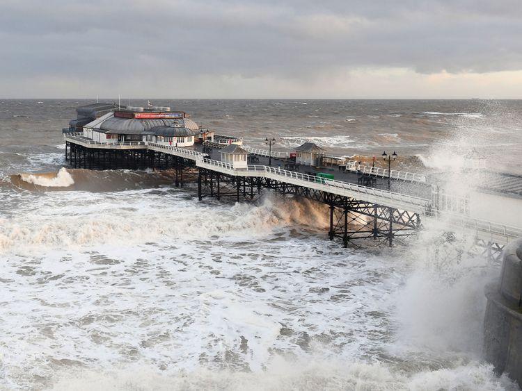 Wellen schlagen um Cromer Pier in Norfolk zusammen
