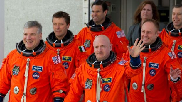 Mark Kelly (C, waving) commanded the space shuttle Endeavour's final mission