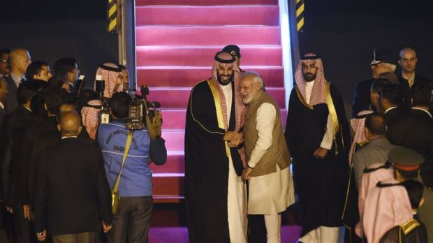 Mohammed bin Salman (L) shakes hands with Narendra Modi at the airport in New Delhi