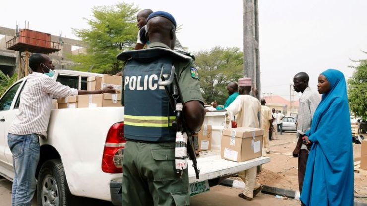 A police officer oversees the distribution of election materials in Yola
