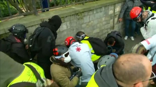 A paramedic attends to the protester with an injured hand