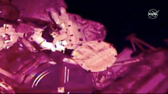 Astronauts Nick Hague and Christina Koch float outside the International Space Station