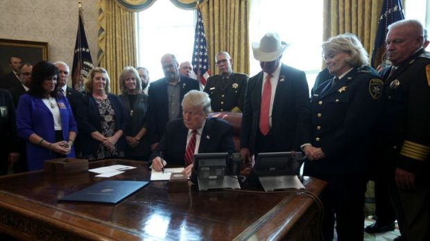 Trump signed the veto, surrounded by various officials