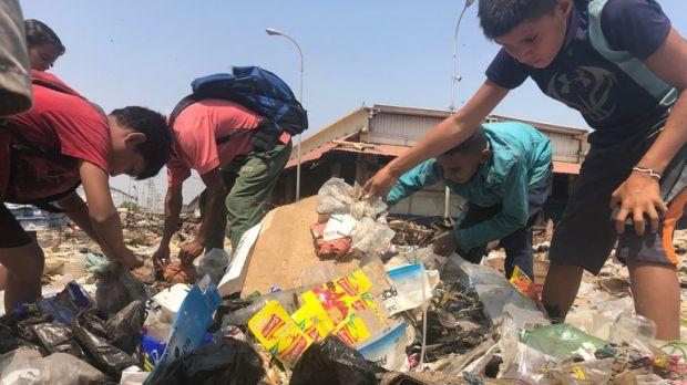 Children rifle through rubbish for food
