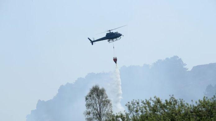 Se está utilizando un helicóptero para arrojar agua al fuego.