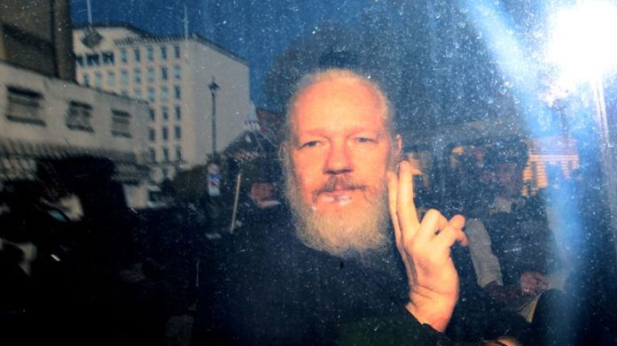 Julian Assange, when he arrives at Westminster Magistrates Court from a police vehicle, points to the media