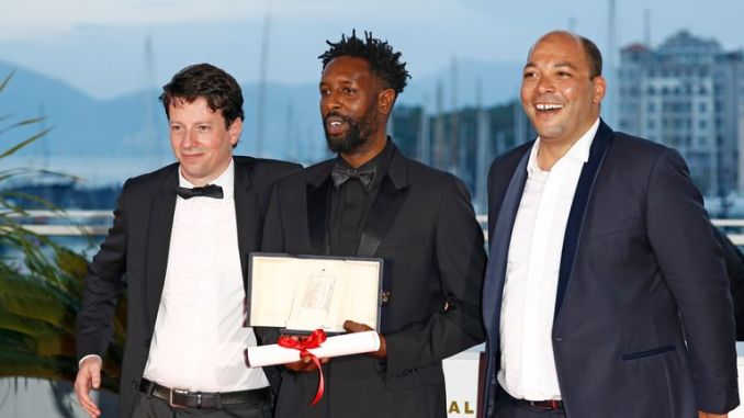 """CANNES, FRANCE - MAY 25: Director Ladj Ly (C), winner of the Jury Price award for his film """"Les Miserables"""" poses with producers Christophe Barral (L) and Toufik Ayadi (R) at thewinner photocall during the 72nd annual Cannes Film Festival on May 25, 2019 in Cannes, France. (Photo by John Phillips/Getty Images)"""