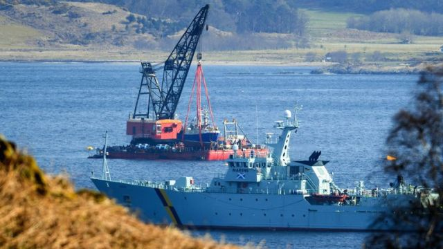 A fisheries protection vessel maneuvers near the specialist lifting barge as it recovers Fishing Trawler the Nancy Glen from Loch Fyne