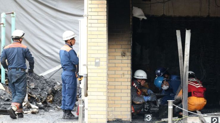 Investigators inspect the scene where 33 people died in a fire at the Kyoto Animation company building