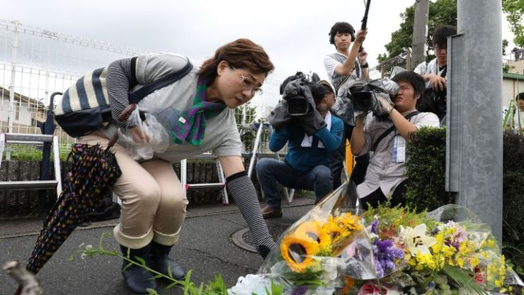 Residents place flowers for victims of the fire