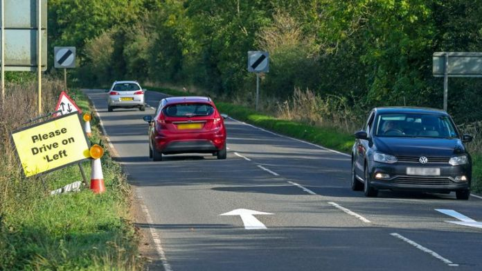 PIXEL NUMBER PLATES BY OFFICE OF IMAGES PA. Signs and arrows were placed on Highway B4031 outside RAF Croughton, Northamptonshire, where Harry Dunn, 19, died from a frontal collision in August.
