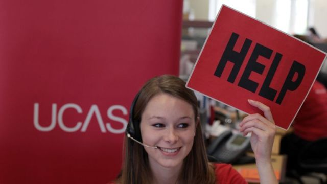 CHELTENHAM, ENGLAND - AUGUST 18: Sam Wathen, an employee in the UCAS clearing house call centre calls for assistance and advice from a supervisor as she answers a student's enquiry as she prepares to assist A-level students ahead of results day on August 18, 2010 in Cheltenham