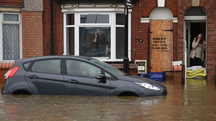 Woman stands behind sandbags in Doncaster