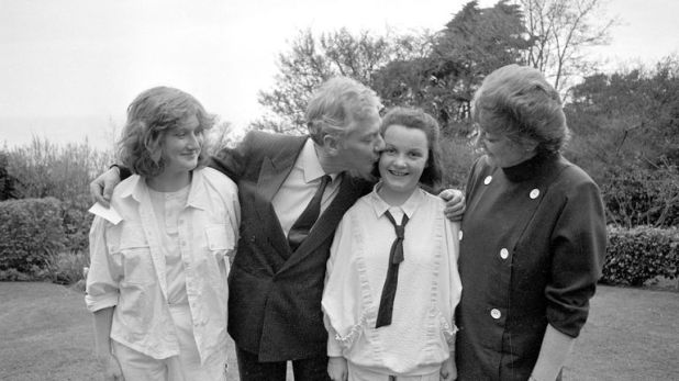 Gay Byrne kisses his daughter Suzy(12) on the day of her Confirmation watched by Crona(15) looks on