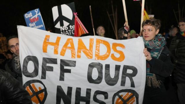 """NHS nurses and doctors protest outside Buckimngham Palace , London, during a """"Hands off our NHS"""" protest against Donald Trump, who is in the capital as Nato leaders gather to mark 70 years of the alliance."""