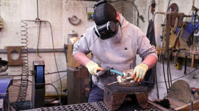 Fettler Piotr Lichon works on a mask during the casting of the British Academy of Film and Television Awards (BAFTA) masks at a foundry in West Drayton, west London, ahead of the ceremony on February 2