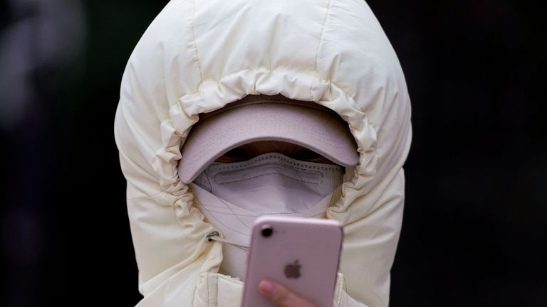 A woman wearing a mask and her hood pulled tight checks her phone in Shanghai
