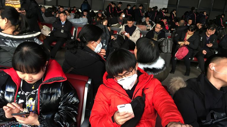 Passengers wearing face masks wait for their train to Wuhan at Beijing West railway ahead of Chinese New Year