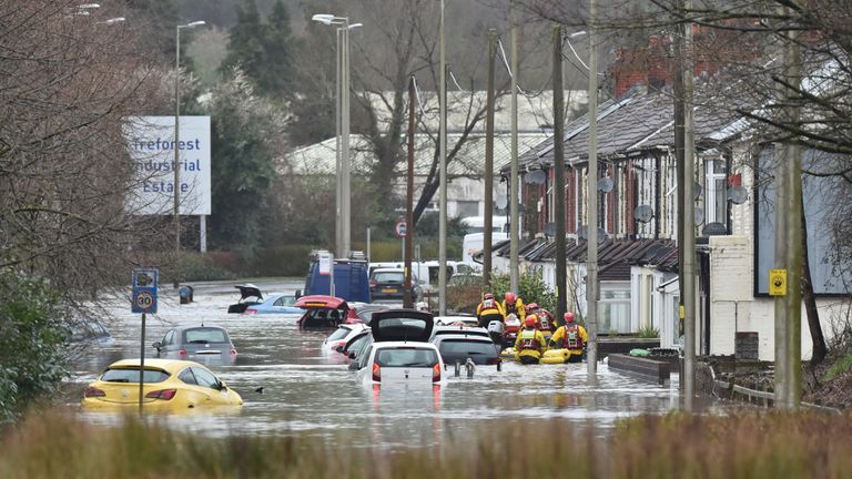A member of the public is rescued from a flooded house in Oxford Street in Nantgarw, Wales as Storm Dennis hit the UK.