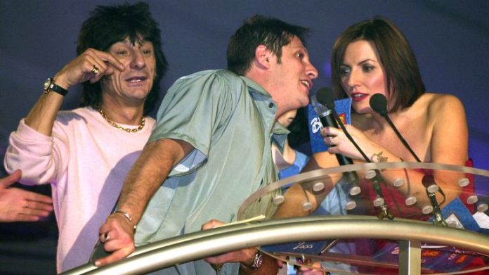 Brandon Block walks on stage to have a word with the host of the ceremony Davina McCall and interrupt the Rolling Stones guitarist Ronnie Wood in 2000